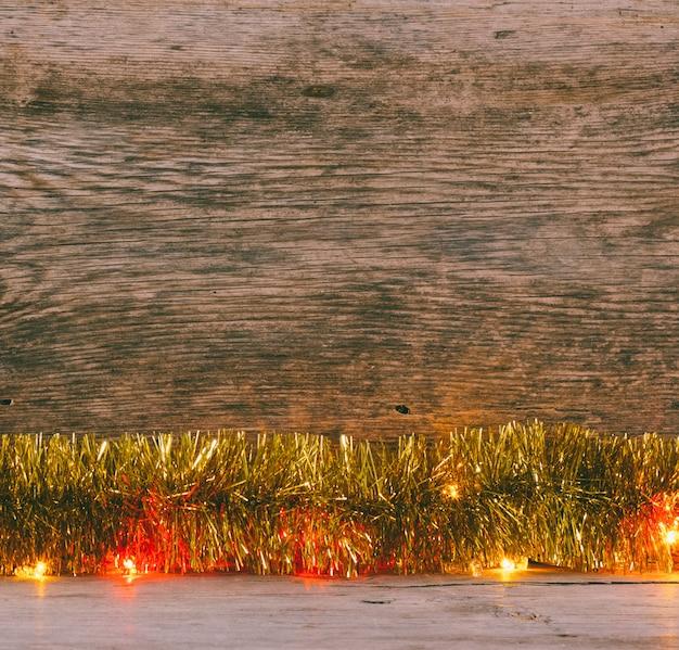 Праздничный новогодний фон. золотая мишура и огни гирлянды на досках старый сарай. тонированное фото