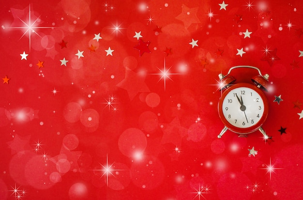 Festive christmas background with alarm clock on red background in minimal style.