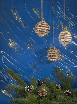 Festive christmas background with christmas tree branch, pine-cones and  wicker holiday balls