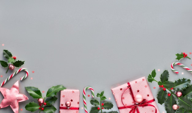 Праздничный новогодний фон с розовыми подарочными коробками, полосатыми леденцами, безделушками и декоративными звездами, геометрическим креативным плоским макетом на серой бумаге с копией пространства