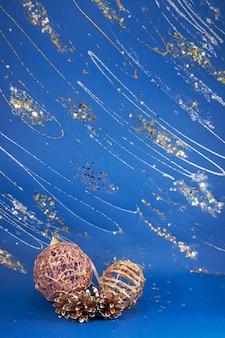 きらめきと星と青い装飾的な冬の背景にお祝いのクリスマスボールと松ぼっくりの構成(青いボール紙のテクスチャ保存)