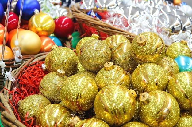 Праздничные новогодние шары разных цветов в корзине на крупном плане витрины