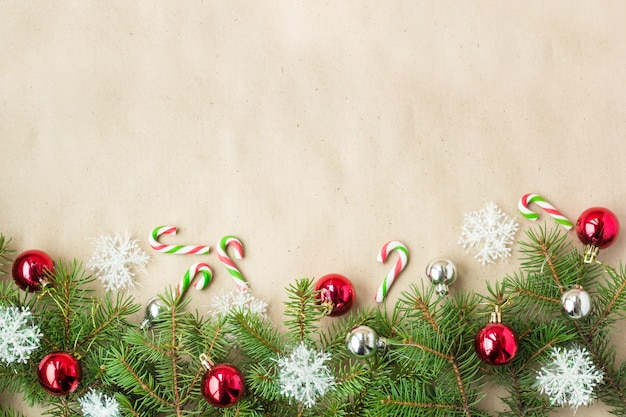 Festive christmas border with red and silver balls on fir branches and snowflakes on rustic beige background