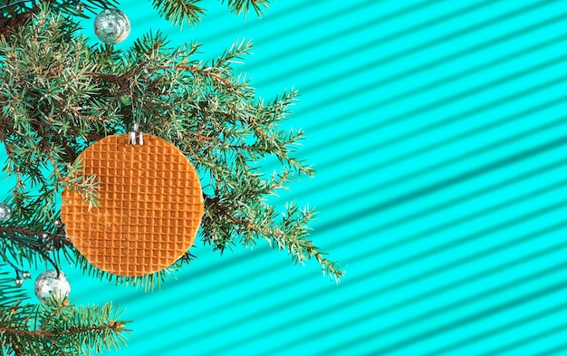 Festive christmas card, banner or postcard with branch of christmas tree with cones and decorated with waffle on turquoise table, streaks of light from the sun on the table, selective focus