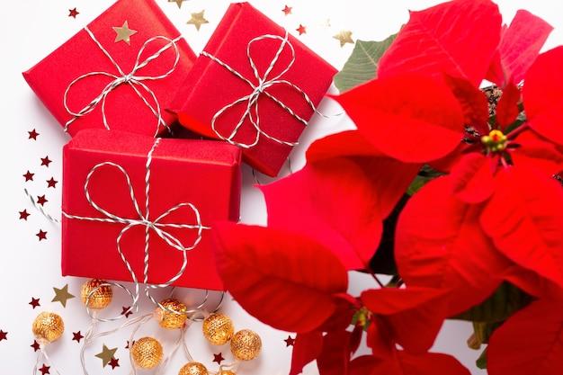 赤いポインセチアの花、包まれたギフト、白いテーブルに紙吹雪とお祝いのクリスマスカード