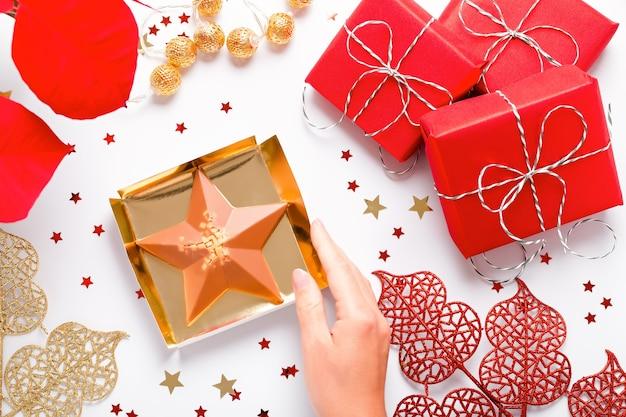 赤いポインセチアの花、包まれたギフト、金色の装飾、白い卓上に紙吹雪、コピースペース、上面図が付いたお祝いのクリスマスカード。赤と金のクリスマスの背景