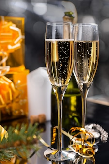 ゴールドで包まれたギフトと回転したゴールデンパーティーストリーマーを備えた2つのエレガントなフルートのお祝いのクリスマスシャンパン