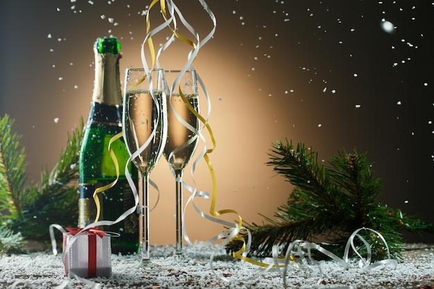 Праздничная рождественская композиция с бокалами для шампанского, подарком и снегом. изображение на темном фоне с подсветкой