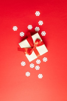 Festive christmas composition with snowflakes and gift box on red . winter . flat lay, top view, copyspace