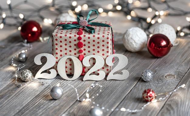 Праздничная рождественская композиция с деревянными числами 2022, подарочной коробкой и елочными шарами на размытом фоне с боке.