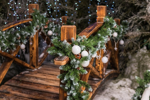 Festive christmas decor near the house. street decoration for winter holidays.fir branches with white christmas balls ornate the wooden bridge in the garden.concept happy christmas, new year.