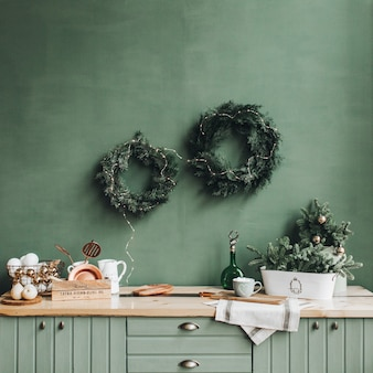 Festive christmas decorations on the kitchen with handmade wreath made of fir branches, gold and white toys