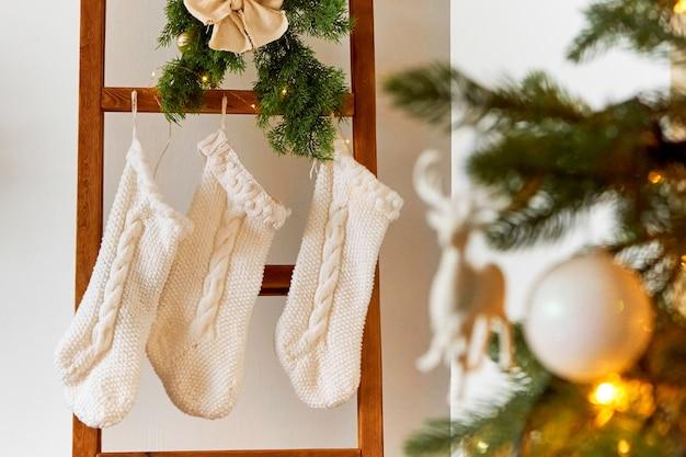 Праздничные новогодние украшения светлой комнаты с елкой и вязанными носками для подарков деду морозу.