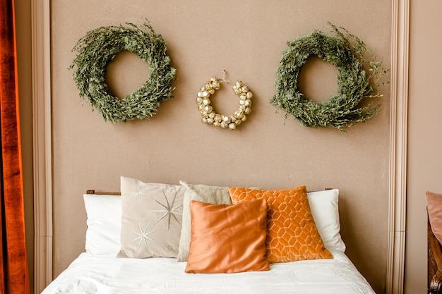 モミの枝の金のおもちゃで作られた花輪とインテリアの寝室のお祝いのクリスマスの装飾