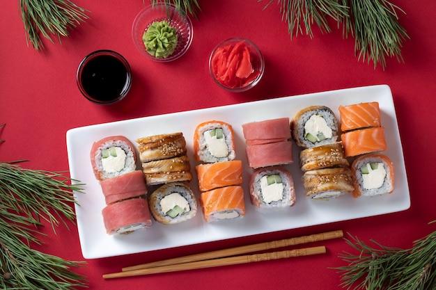 赤い背景の白いプレートにフィラデルフィアチーズをセットしたサーモン、マグロ、ウナギの寿司とお祝いのクリスマスディナー。醤油、わさび、生姜の酢漬け、お寿司のスティックを添えて。上面図