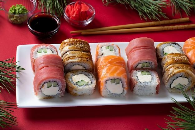 Праздничный рождественский ужин с суши из лосося, тунца и угря с сыром филадельфия на белой тарелке на красном фоне. подается с соевым соусом, васаби, маринованным имбирем и палочками для суши.