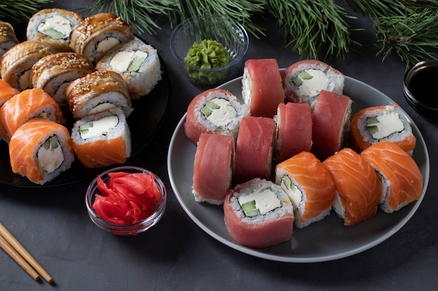 Festive christmas dinner with salmon, tuna and eel sushi set with philadelphia cheese. new year party. closeup on dark background