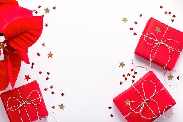 붉은 포인세티아 꽃이 있는 축제 크리스마스 프레임, 포장된 선물, 색종이 조각이 흰색 탁자 위에 있고 복사 공간, 위쪽 전망. 빨간 장식으로 최소한의 크리스마스 배경