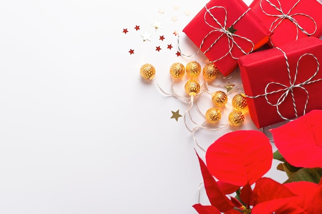 붉은 포인세티아 꽃, 포장된 선물, 황금 장식, 색종이 조각이 흰색 탁자 위에 있는 축제 크리스마스 프레임, 복사 공간, 위쪽 전망. 빨간색과 금색의 크리스마스 배경