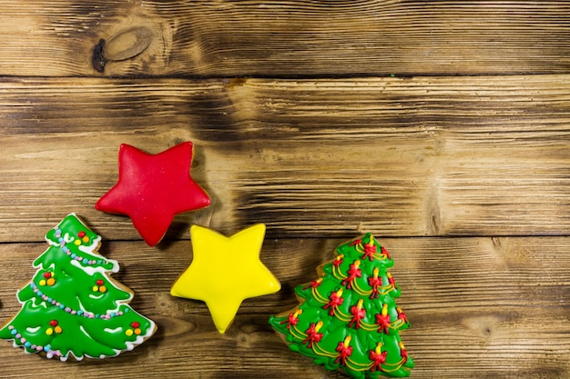 Festive christmas gingerbread cookies in the shape of christmas tree and stars. tasty gingerbreads on wooden table. top view