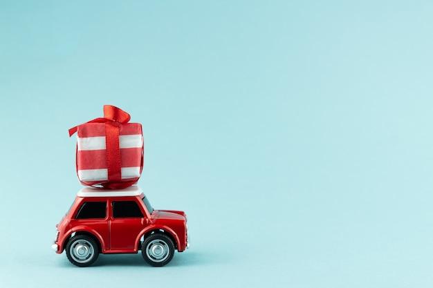 青のギフトボックスを運ぶ赤いおもちゃの車とお祝いのクリスマスグリーティングカード