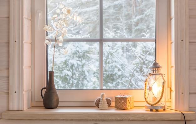 屋内の冬の木製の窓枠にお祝いのクリスマスランタン、ギフト、天使。クリスマスの装飾、スカンジナビアスタイル