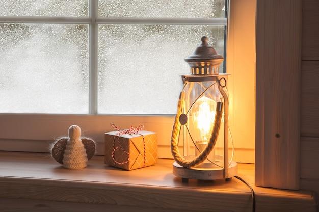 Праздничный рождественский фонарь, подарки и ангел на деревянном подоконнике зимой в помещении. новогоднее украшение, скандинавский стиль