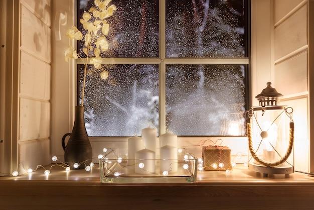 屋内の冬の木製の窓枠にお祝いのクリスマスランタン、ギフト、キャンドル。クリスマスの装飾、スカンジナビアスタイル