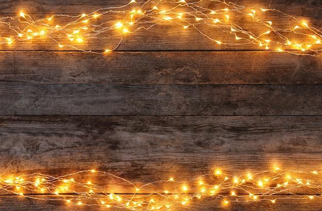 木製の背景にお祝いのクリスマスライト