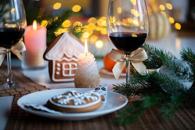 와인 한 잔과 부엌 저녁 식사 테이블에 불타는 촛불 축제 크리스마스 분위기