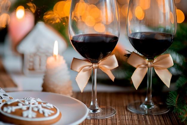 와인 두 잔과 부엌 식탁에 불타는 촛불이있는 축제 크리스마스 분위기
