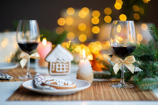 Festive christmas mood with a glass of wine and a burning candle on the kitchen dinner table