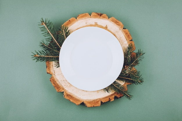 Festive christmas natural style table setting with white plate on wood cut platters
