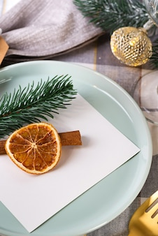 Festive christmas and new year details table setting with dry orange and cinnamon on a gray textile. dining place decorated