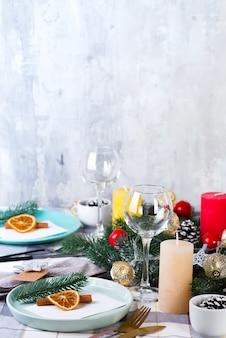 Festive christmas and new year table setting with dry orange and cinnamon on a gray textile. dining place decorated with pine cones, branches and candles
