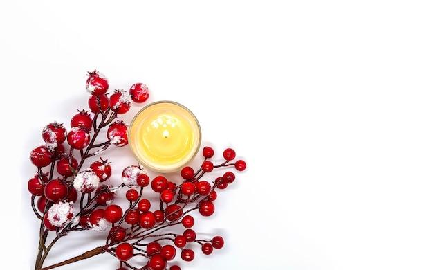雪の中で赤いヒイラギの果実と白い背景の上のワックスキャンドルを燃やすとお祝いのクリスマスまたは新年の構成