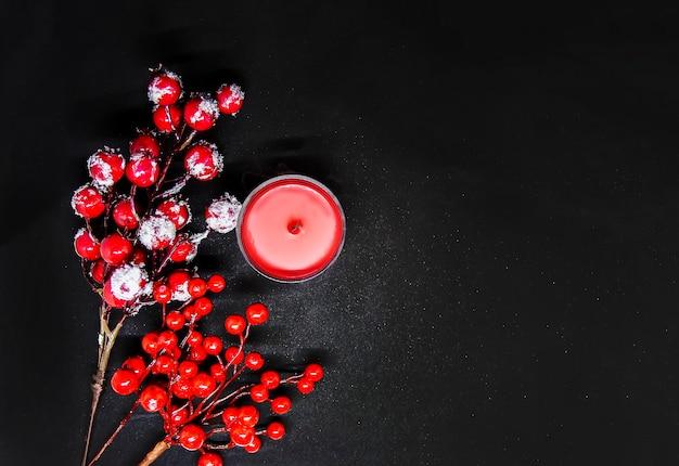 雪とワックスキャンドルの赤いヒイラギの果実とお祝いのクリスマスまたは新年の構成。