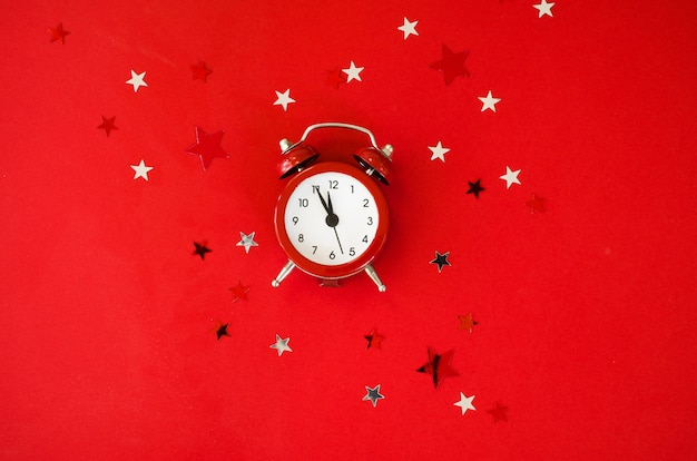 Festive christmas setting with alarm clock on red background in minimal style.