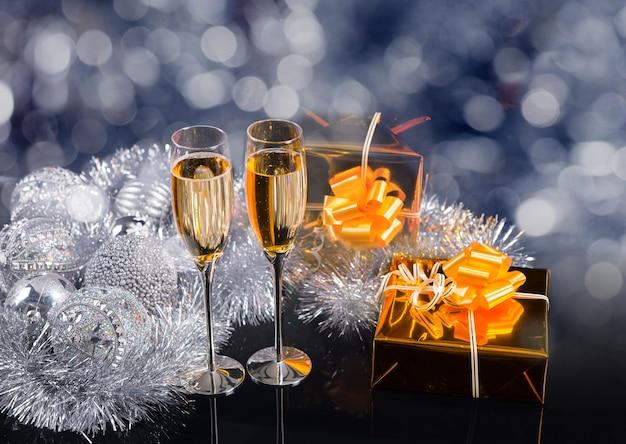 コピースペースのあるお祝いのクリスマスの静物-ゴールドラッププレゼント、シルバーティンセルガーランド、装飾装飾品のきらびやかな静物のシャンパングラスのペア