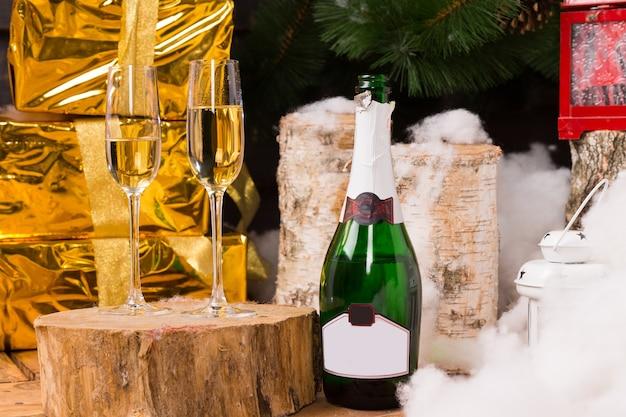 金色の光沢のある包装紙で包まれたギフトボックスの横にある切り株、ボトル、丸太、モミの木、ランタン、雪の上に2つのシャンパンフルートがあるお祝いのクリスマスの静物
