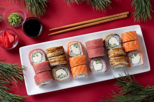 赤い背景の白いプレートにサーモン、マグロ、ウナギ、フィラデルフィアチーズをセットしたお祝いのクリスマス寿司。醤油、わさび、生姜の酢漬け、お寿司のスティックを添えて。上から見る
