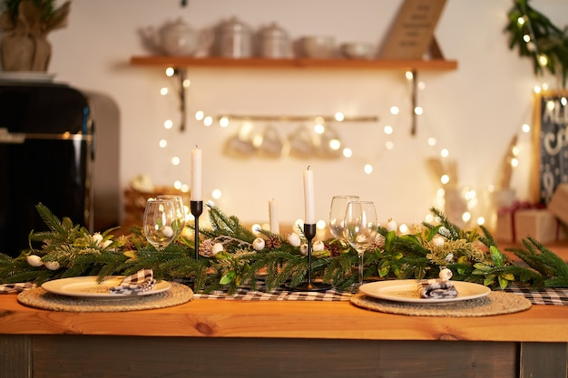 The festive christmas table is decorated with branches of a christmas tree, candles and garlands