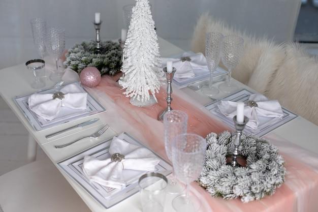 冬の装飾と白いキャンドルの間にテーブルクロスでお祝いのクリスマステーブルの設定