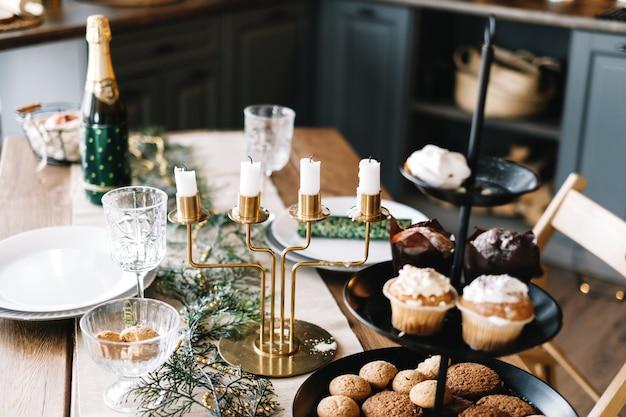 装飾が施されたキッチンで甘いクッキーとケーキが付いたお祝いのクリスマステーブル。
