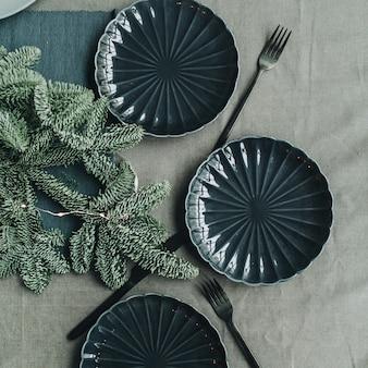 モミの枝、花輪、プレート、ナイフ、フォークで飾られたお祝いのクリスマス感謝祭のテーブル
