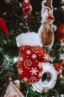 Праздничная елка украшенная елочной игрушкой красная варежка празднование зимнего праздника