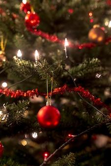 Праздничная елка украшена традиционными орнаментами в виде огней, красных безделушек и мишуры, крупным планом.