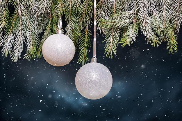 Праздничная елка с серебряными шарами во время снегопада