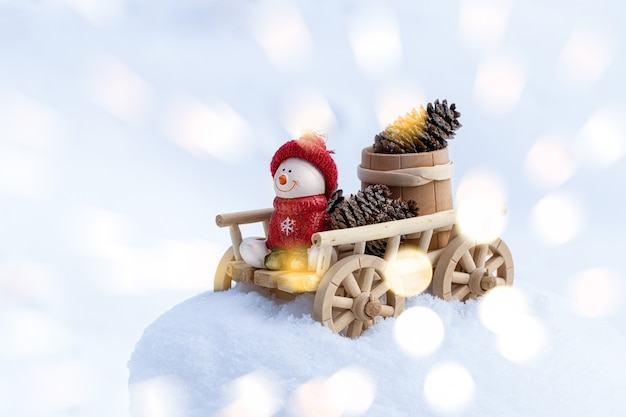 Festive christmas wall with snowman on a wooden cart. happy snowman in winter christmas landscape. merry christmas and happy holidays