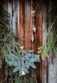 モミの枝、花輪、コーンでお祝いのクリスマスウィンドウの装飾。メリークリスマスの看板と窓枠のつまらないもの